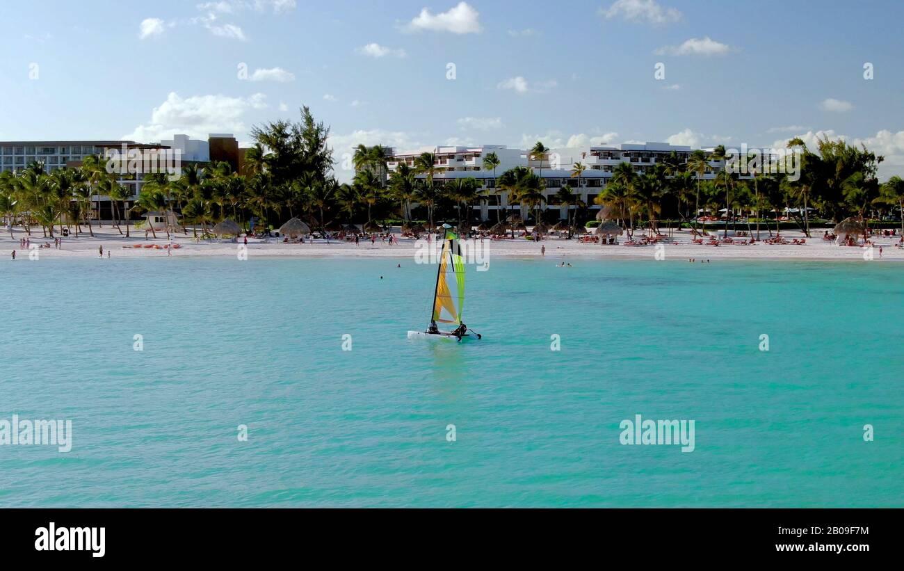 Navegación en el Mar Caribe frente a las costas de Punta Cana, República Dominicana, vacaciones de lujo y resort de vacaciones en el fondo, con arena blanca Foto de stock