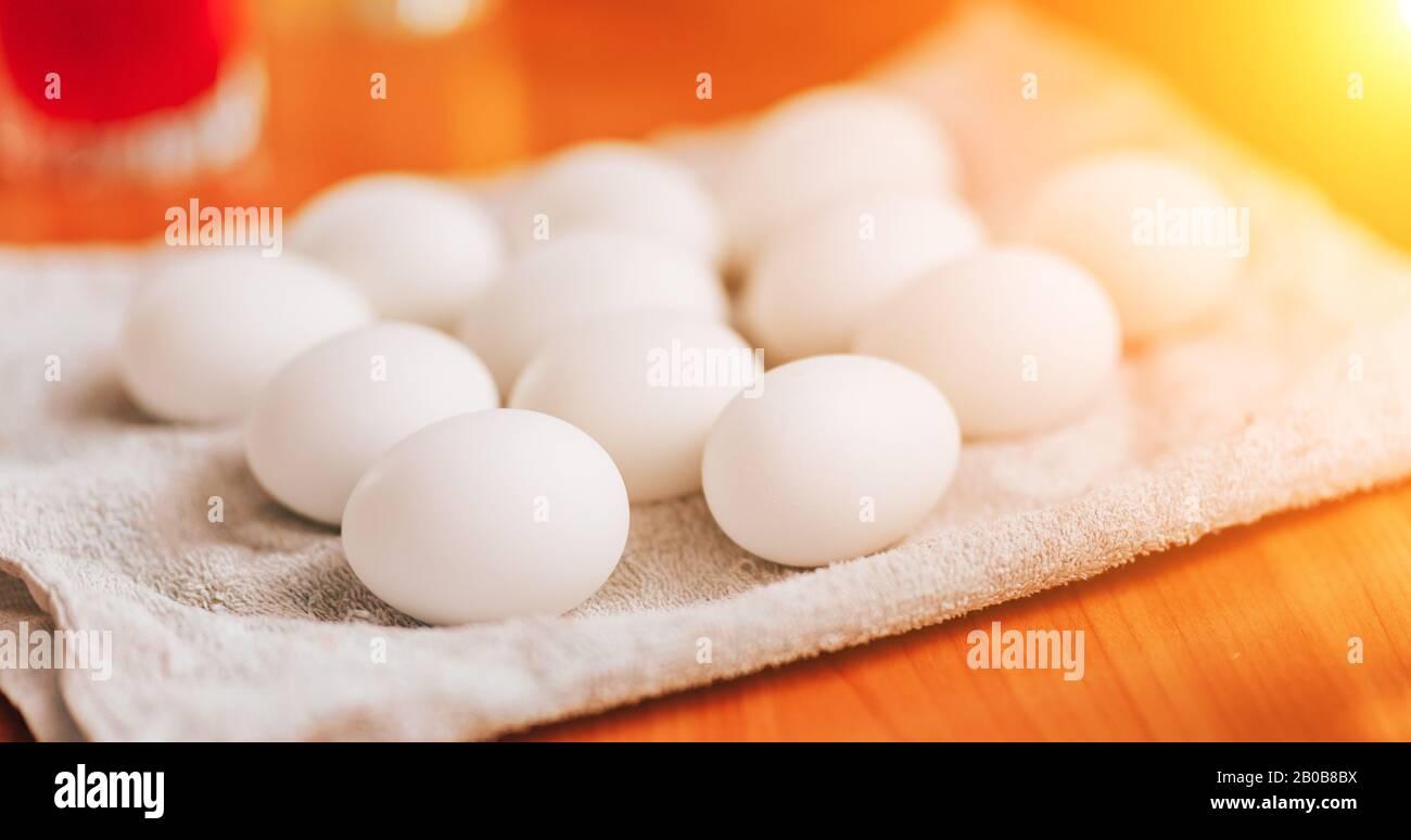 Muchos huevos blancos tumbados en la servilleta se preparan para la pintura Foto de stock