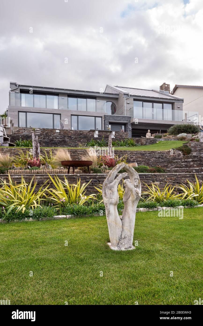 Estatuas en el jardín de terrazas de la propiedad renovada de los años 60 en Fistral, Newquay Foto de stock
