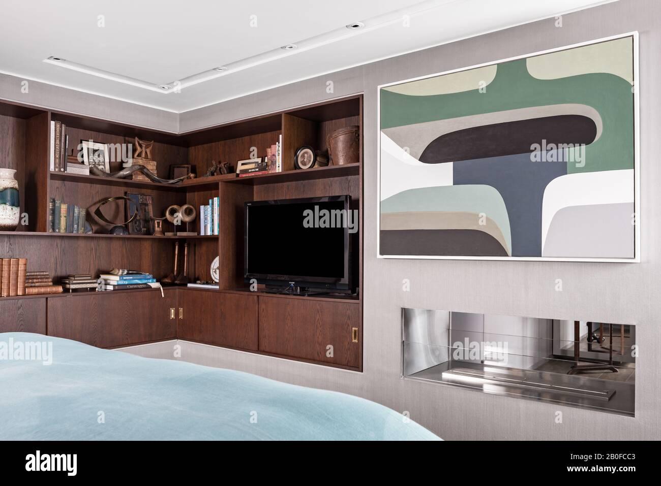 TV en estanterías con paneles de madera y grandes obras de arte en el dormitorio de los modernos apartamentos del oeste de Londres. Foto de stock