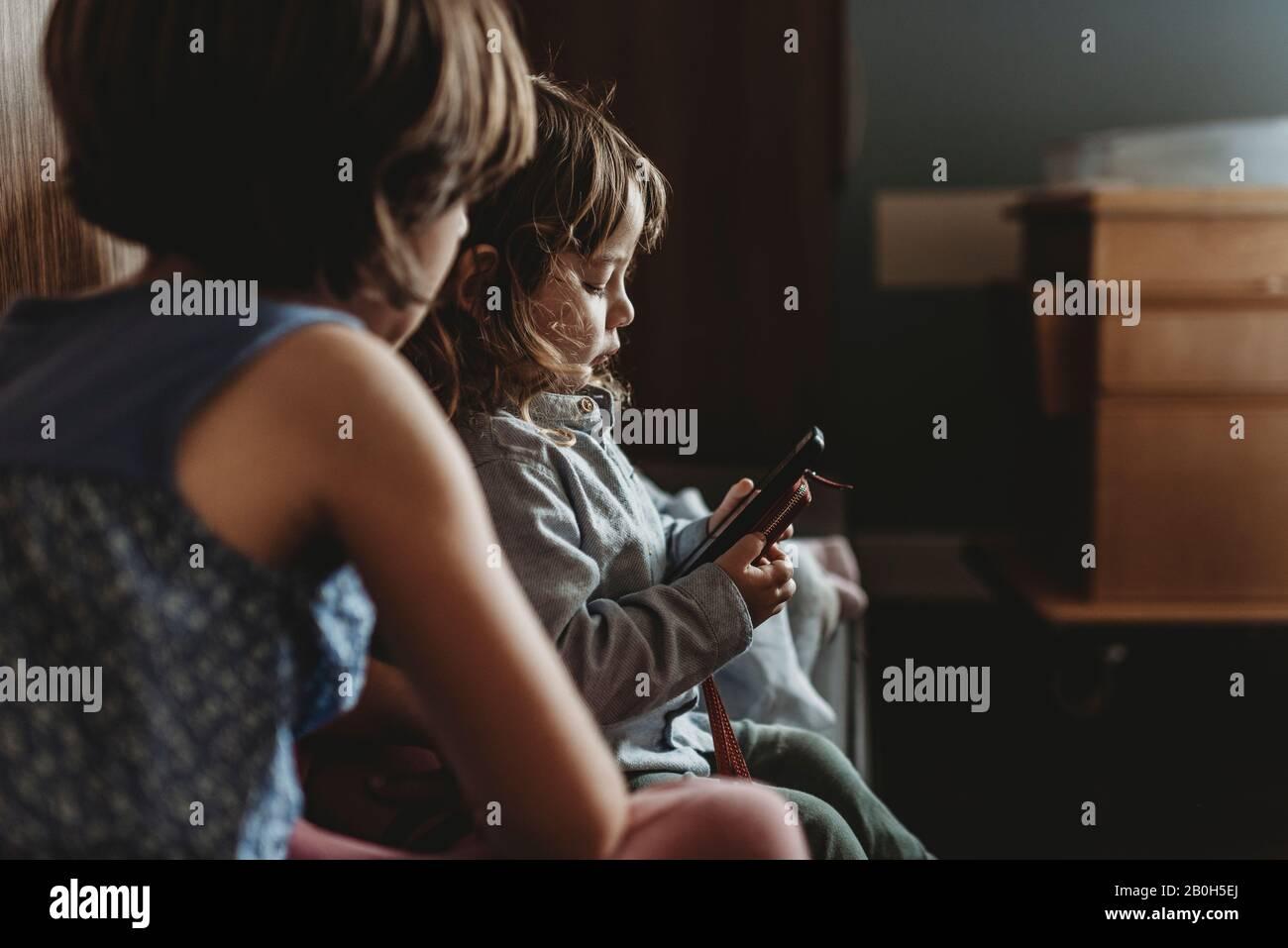 Vista lateral del niño jugando por teléfono en el hospital Foto de stock