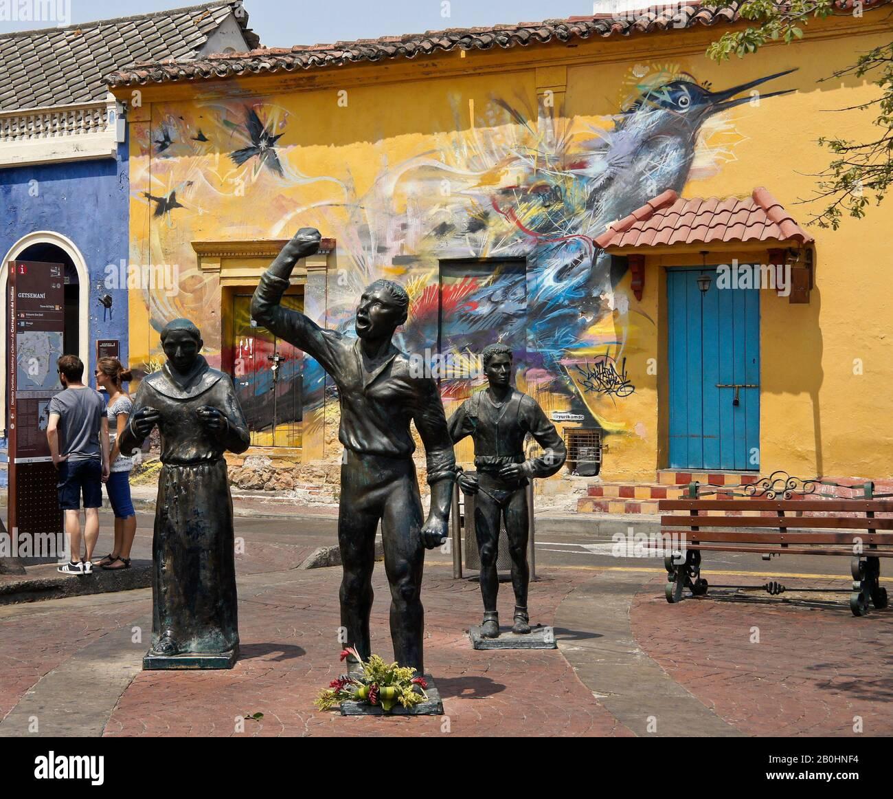 Esculturas de héroes de la independencia en la Plaza Trinidad frente al arte de la calle decorando un edificio colonial en Getsemani, Cartagena, Colombia Foto de stock