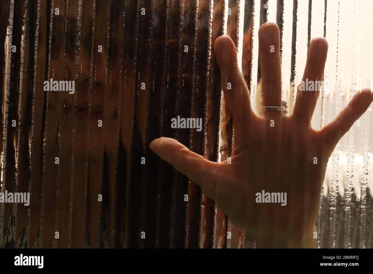 Imagen espeluznante de la niña detrás del cristal con las palmas de las manos sobre el cristal texturizado Foto de stock