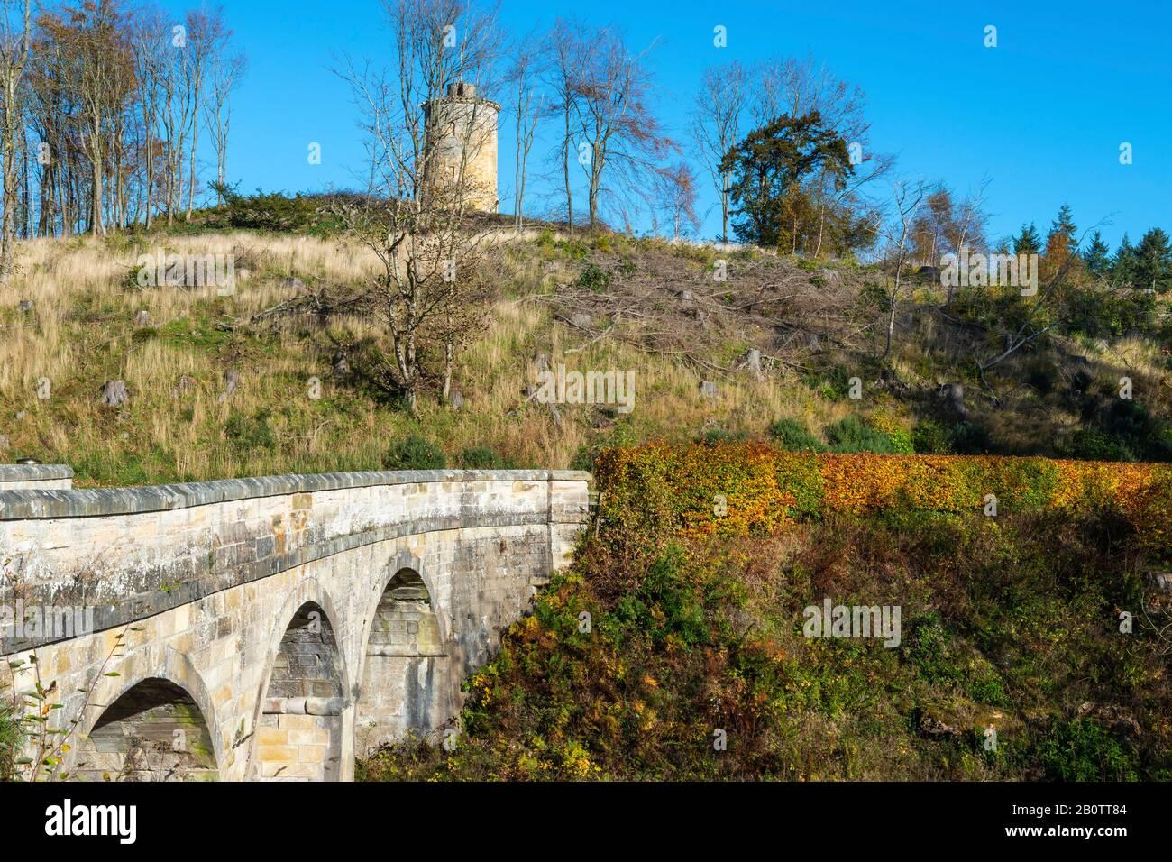 Puente de arco de piedra en la entrada principal con la Torre de la Ley Knight en el fondo, Penicuik Estate, Midlothian, Escocia, Reino Unido Foto de stock