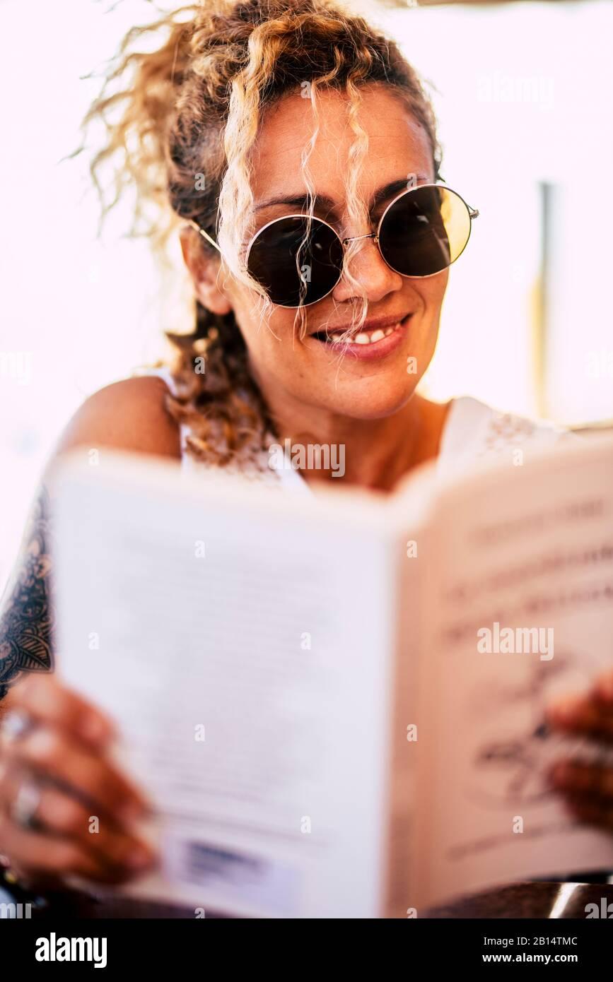 Hermosa mujer caucásica joven de 40 años de edad leer un libro de papel al aire libre - relajarse y estudiar o disfrutar de la lectura - alegre gente feliz y la librería concip Foto de stock