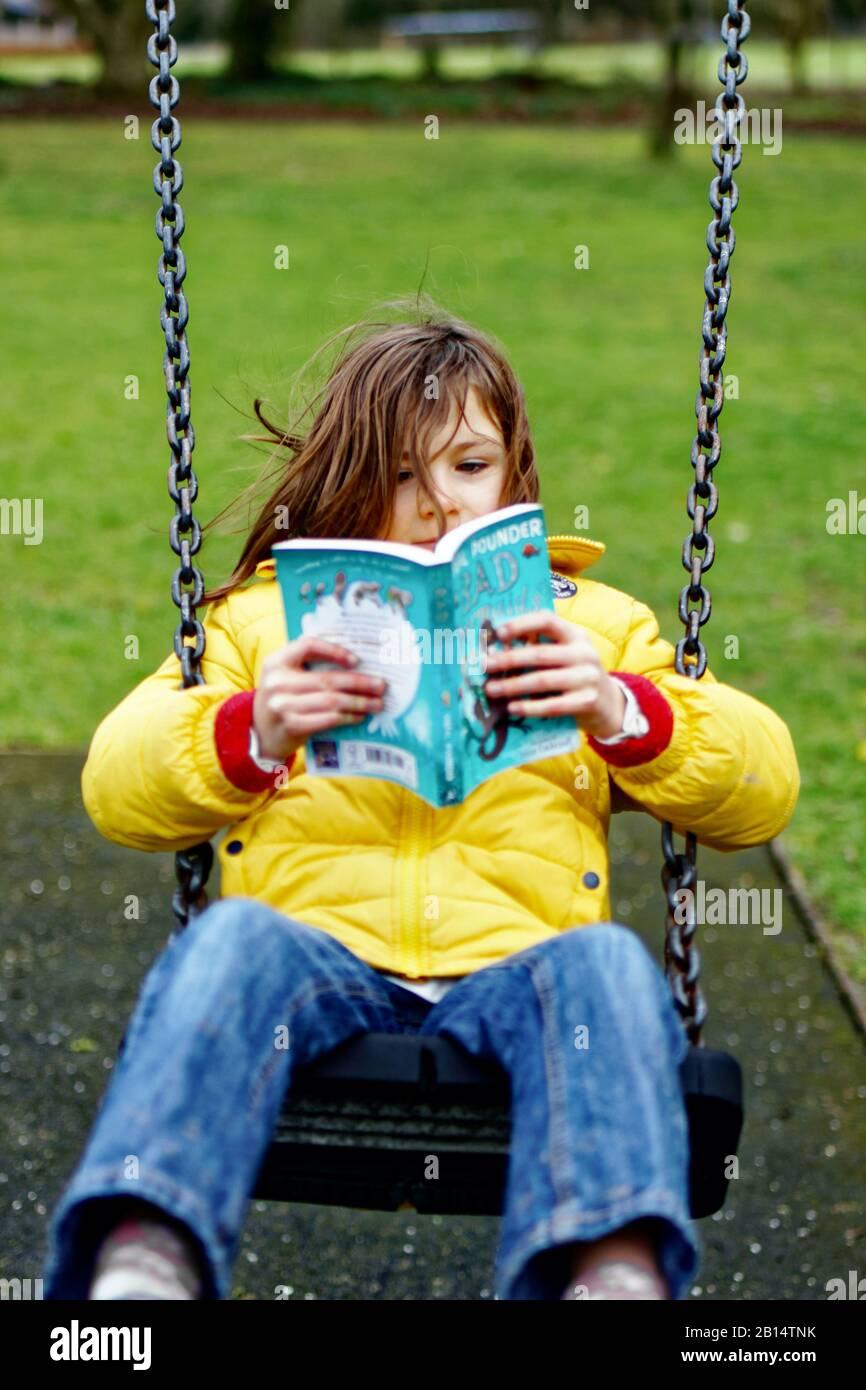 Chica leyendo en un parque Foto de stock