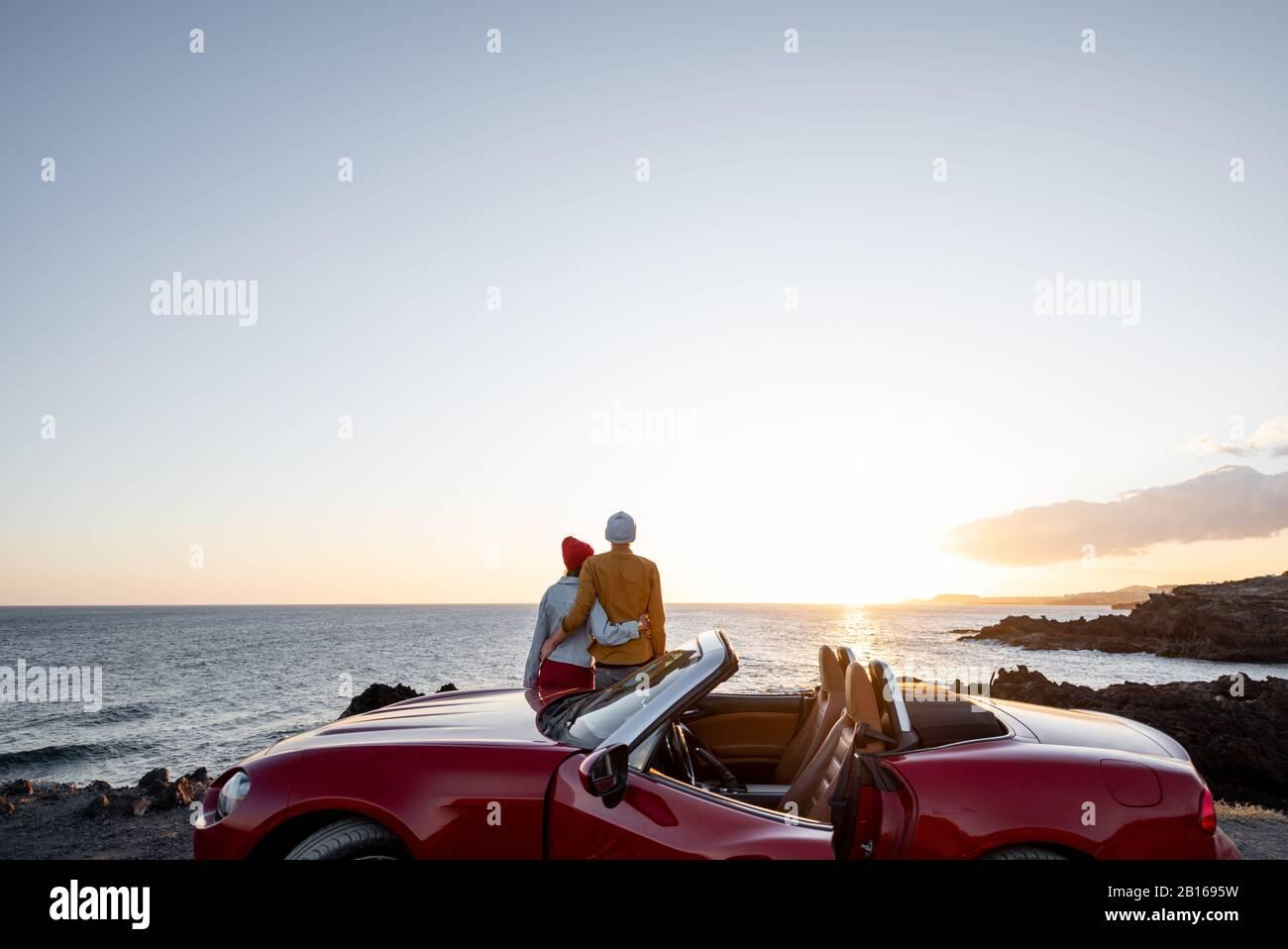 Pareja disfrutando de hermosas vistas sobre el océano, abracándose cerca del coche en la costa rocosa, amplia vista desde el lado con espacio para copias en el cielo Foto de stock