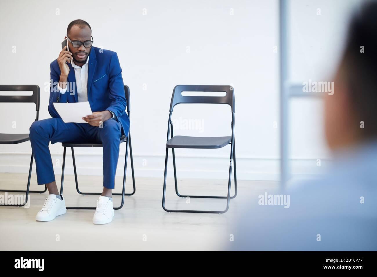 Retrato completo de un hombre afroamericano moderno esperando una entrevista de trabajo detrás de una pared de cristal y hablando por teléfono, espacio de copiado Foto de stock