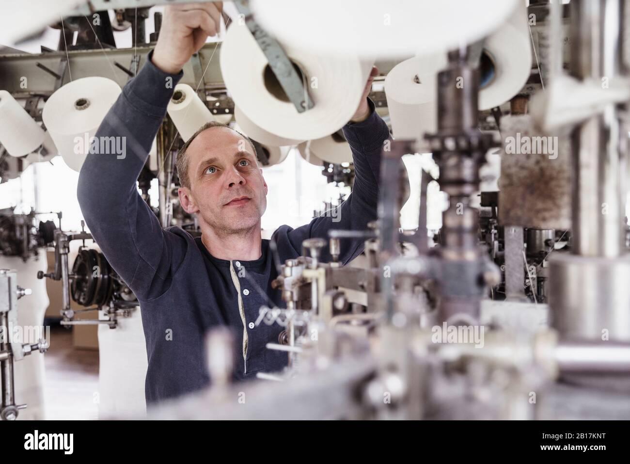 Hombre trabajando en una máquina en una fábrica textil Foto de stock