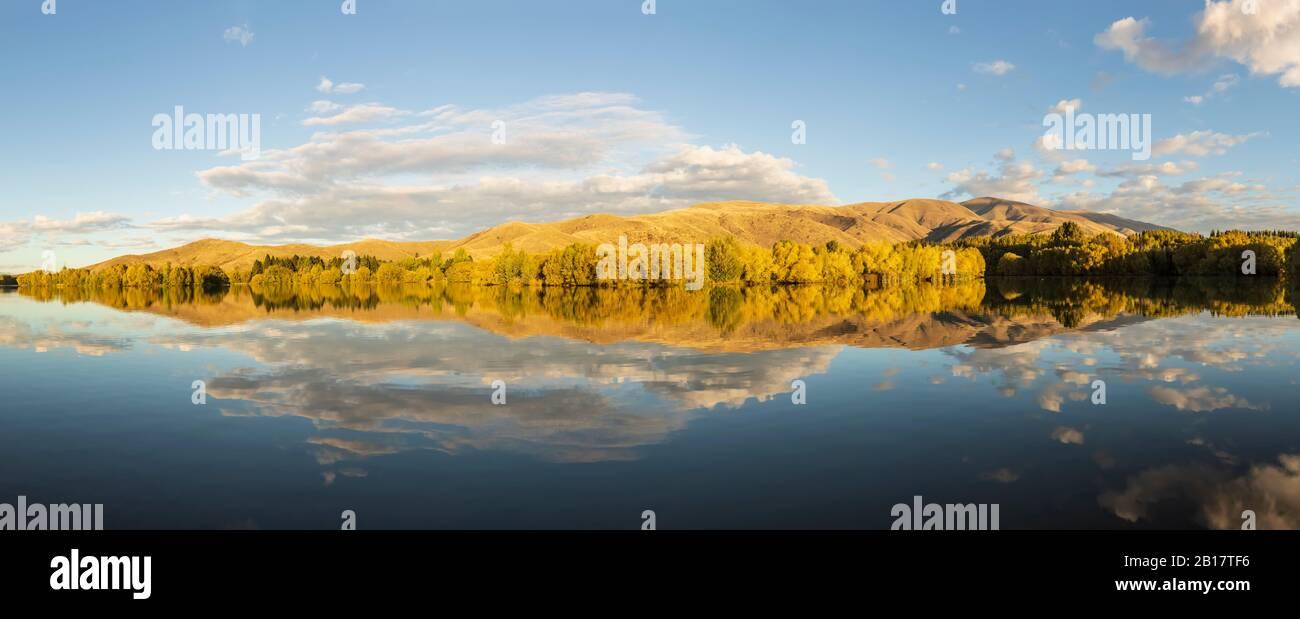Nueva Zelanda, Distrito Franklin, Glenbrook, colinas boscosas que se reflejan en el lago Wairepo Arm en otoño Foto de stock