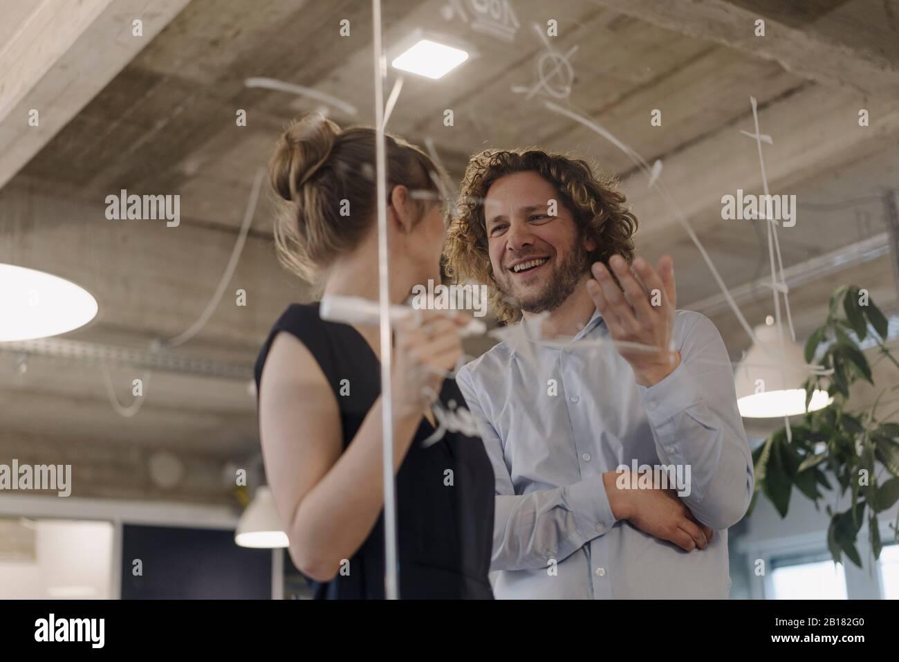 Hombre de negocios sonriente y empresaria trabajando en un proyecto en la oficina Foto de stock