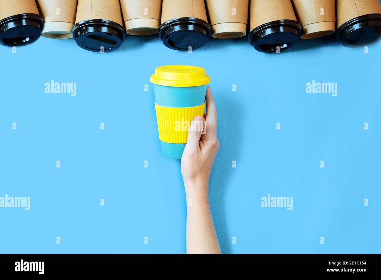 Tazas de café de bambú azul background.One eco taza de café en la mano femenina. Foto de stock