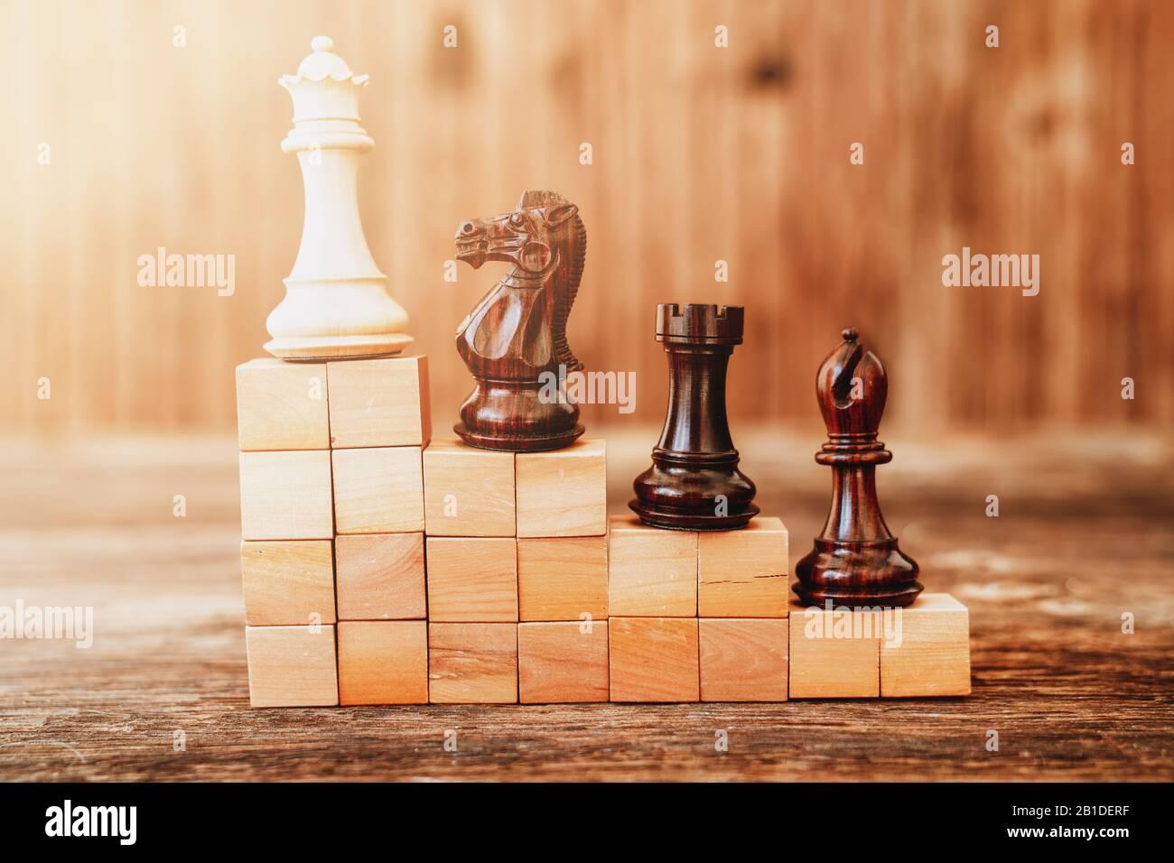Piezas de chees en un edificio de escaleras con bloques de madera, jerarquía de metáforas, clasificación, trabajo en equipo y estrategia en concepto de negocio Foto de stock