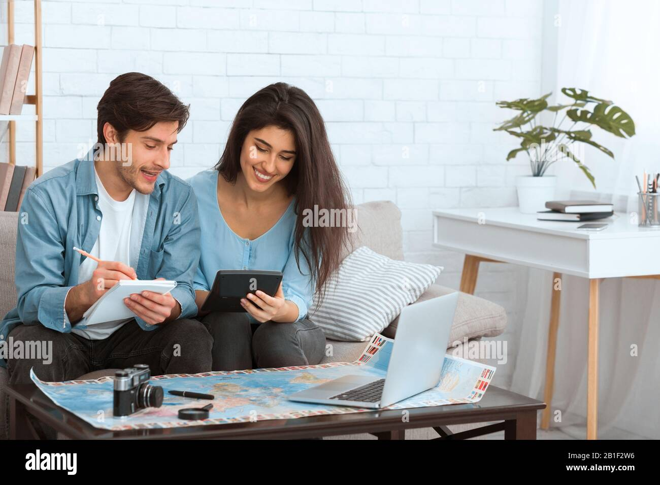 Planear las finanzas. Pareja preparándose para vacaciones y calculando gastos Foto de stock