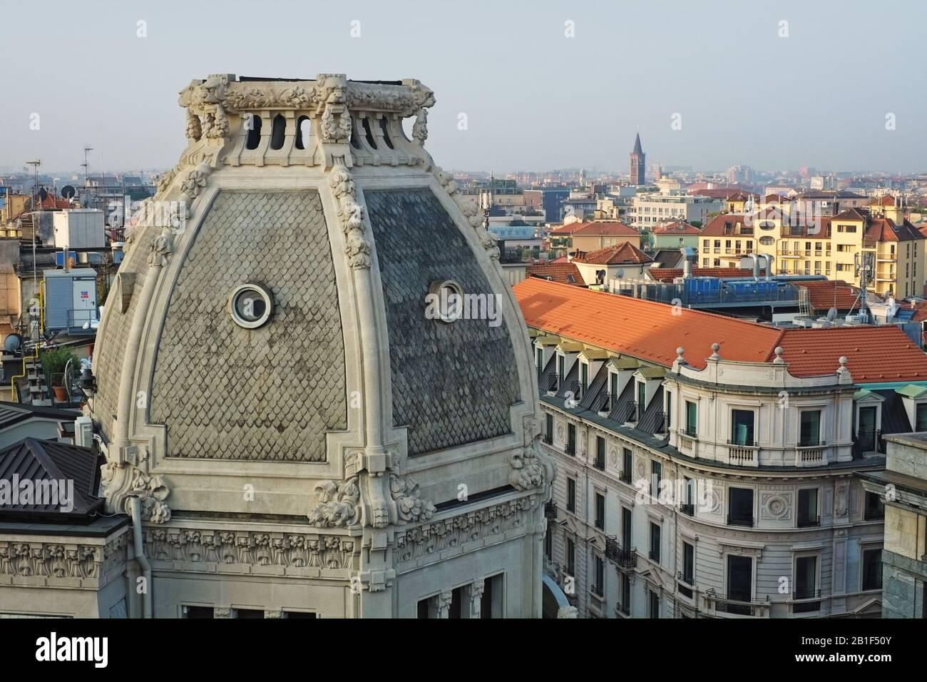 Una vista cercana de la cúpula de techo balaustrada del Palazzo Meroni - leones y guirnaldas florales, ventanas de óculos y la ciudad de Milán en el fondo Foto de stock
