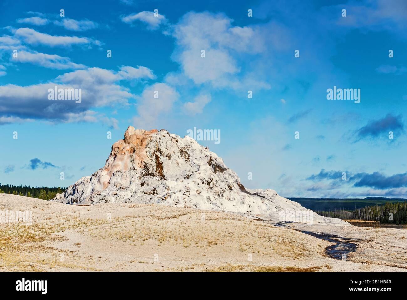Formación de roca géiser humeante contra un cielo azul con nubes blancas. Foto de stock