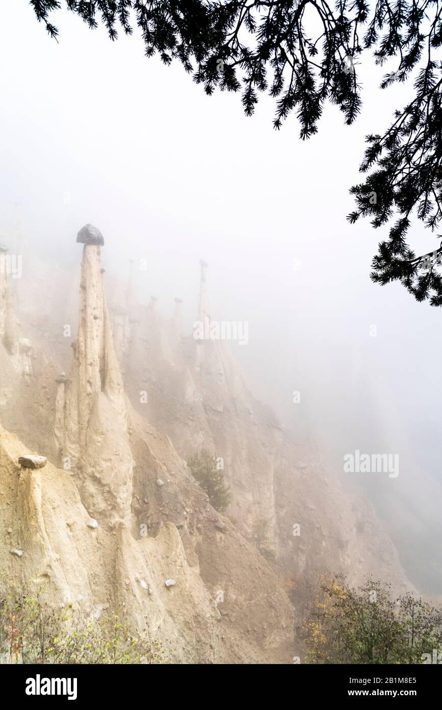 Cielo foggy en otoño sobre la Tierra formaciones rocosas de las Pi�ridas, Perca/Percha, provincia de Bolzano, Tirol del Sur, Italia Foto de stock