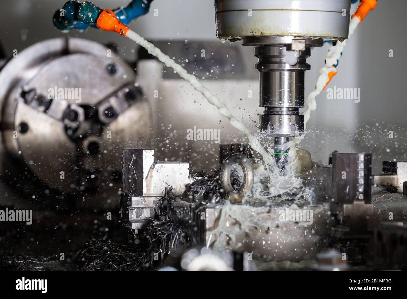 Un proceso de fresado vertical de acero cnc con corrientes de agua refrigerante externas, salpicaduras y muchas virutas de metal. Velocidad de obturación rápida para congelar el movimiento Foto de stock
