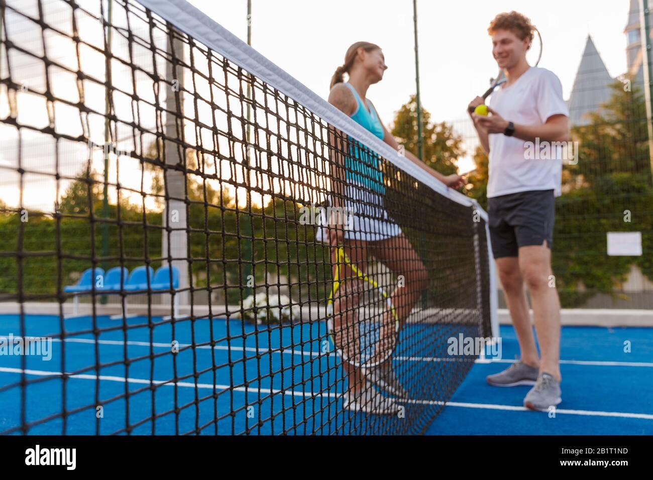 Imagen de un joven sonriente positivo dos jugadores de tenis positivo mujer y hombre al aire libre hablando entre sí sosteniendo raqueta. Foto de stock