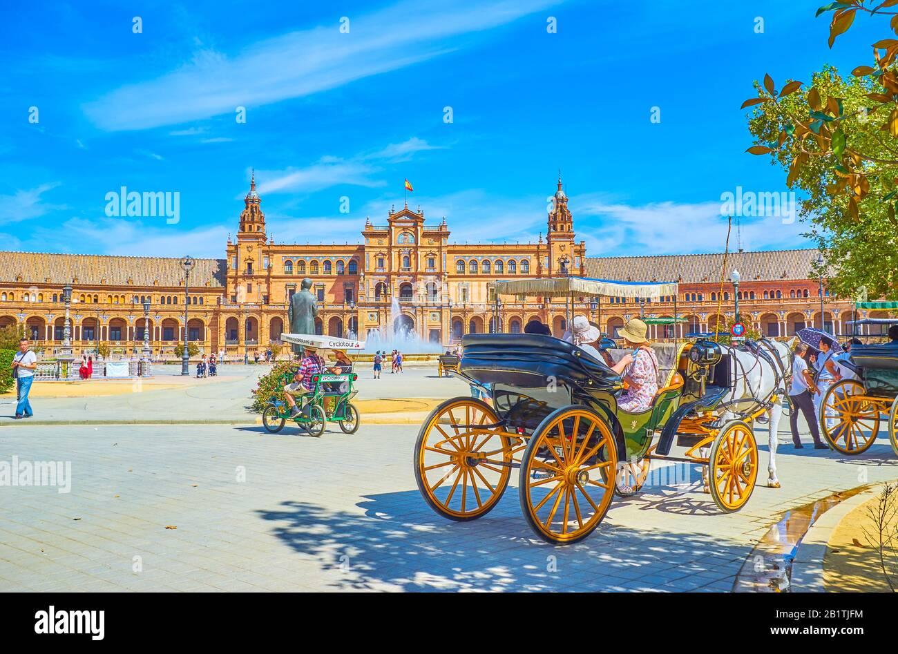 Sevilla, ESPAÑA - 1 DE OCTUBRE de 2019: La línea de carruajes turísticos tirados por caballos a la sombra de los árboles del parque de María Luisa con vistas a la Plaza de España, Foto de stock