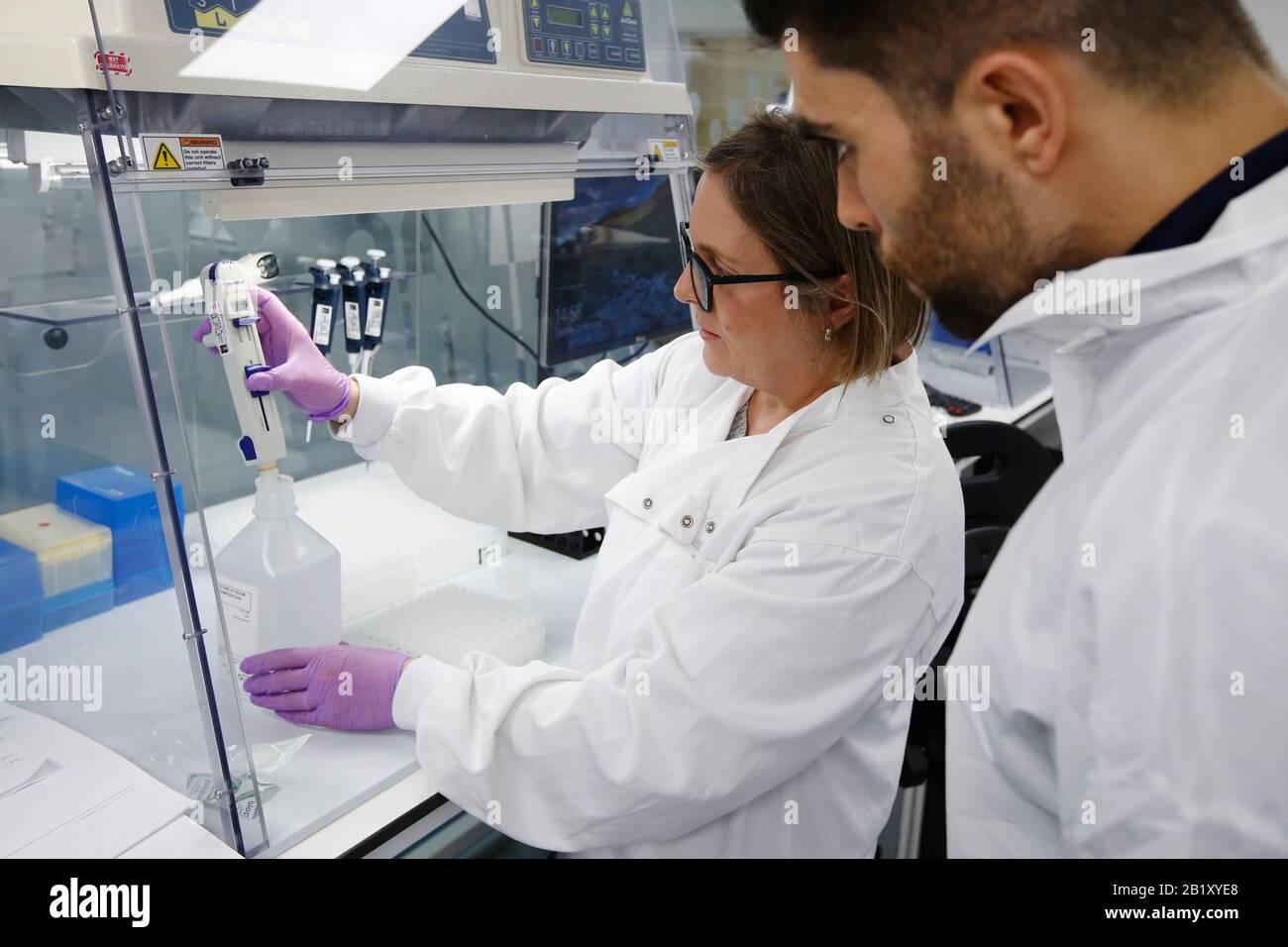 La técnico de producción Fiona Mooney y David Arancon, investigador asociado, dispensan los componentes del primer diseño Coronavirus COVID-19 dete Foto de stock