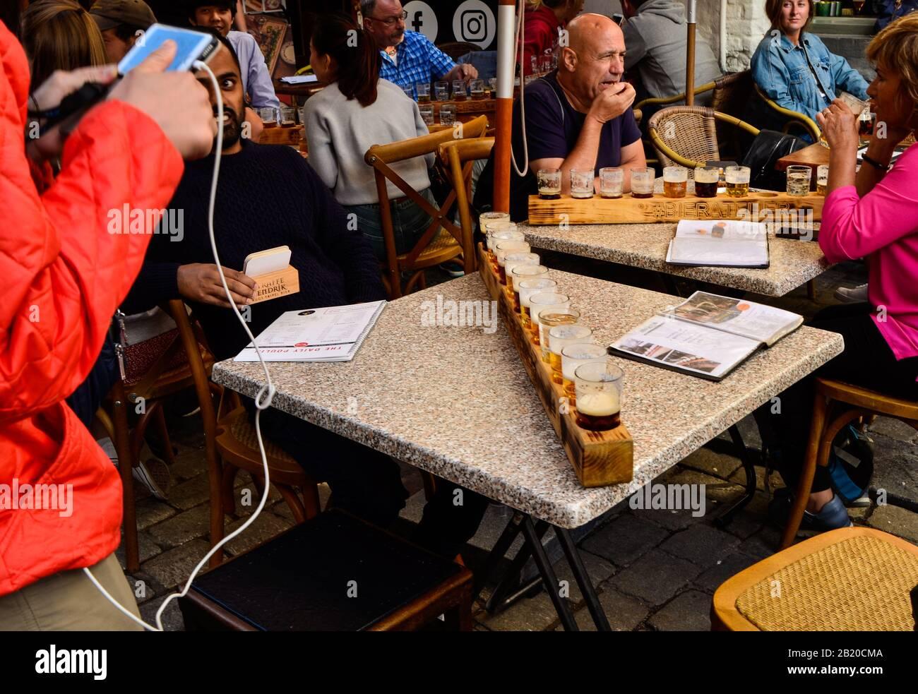 Brujas, Bélgica. Agosto De 2019. Degustación de cervezas artesanales belgas: Doce tazas dispuestas en el portavasos de madera. La gente está sentada en las mesas disfrutando Foto de stock