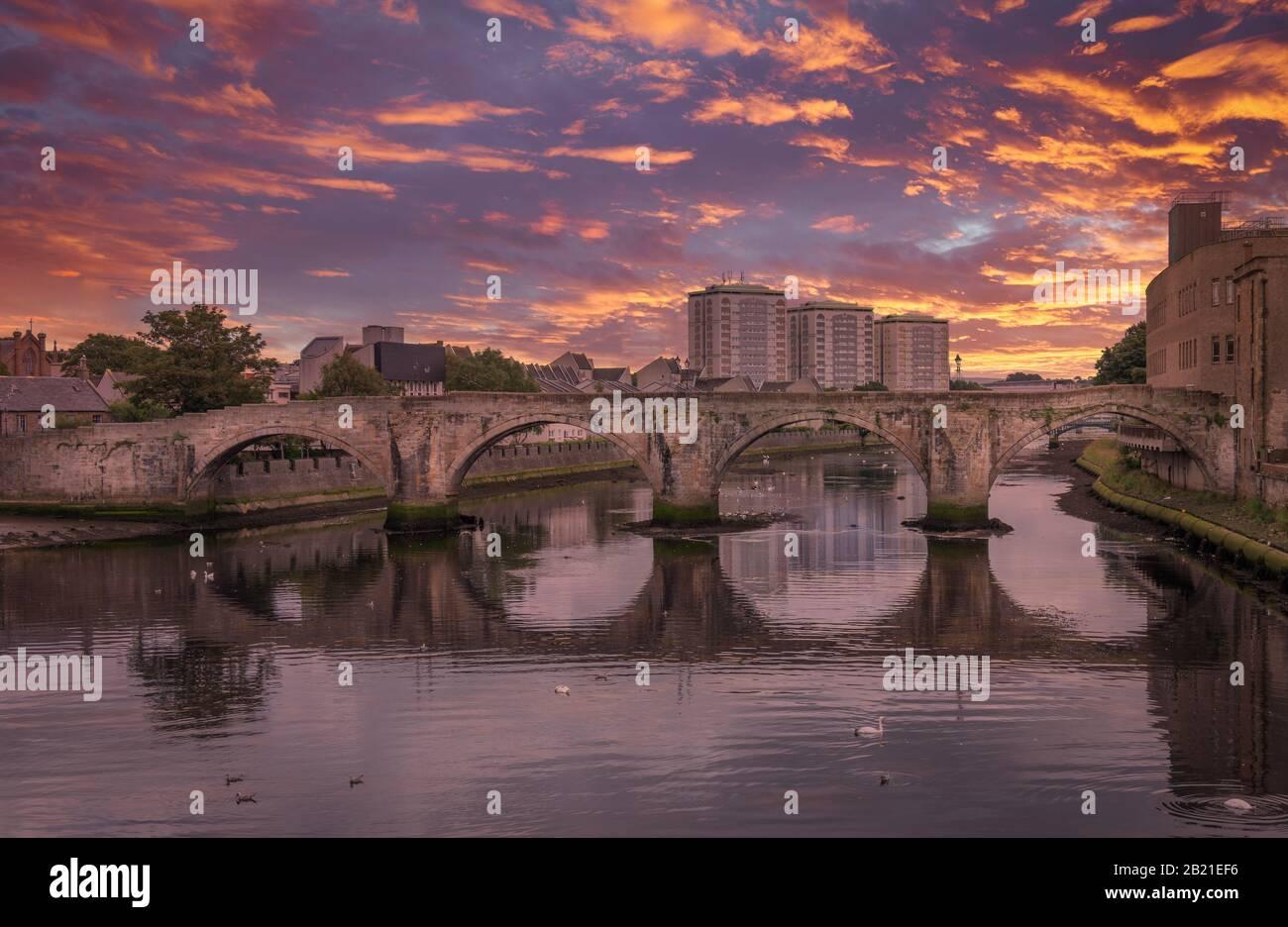 El histórico Puente Viejo de Ayr en Escocia que se extiende por el río Ayr y una espectacular puesta de sol roja sobre la ciudad. Foto de stock