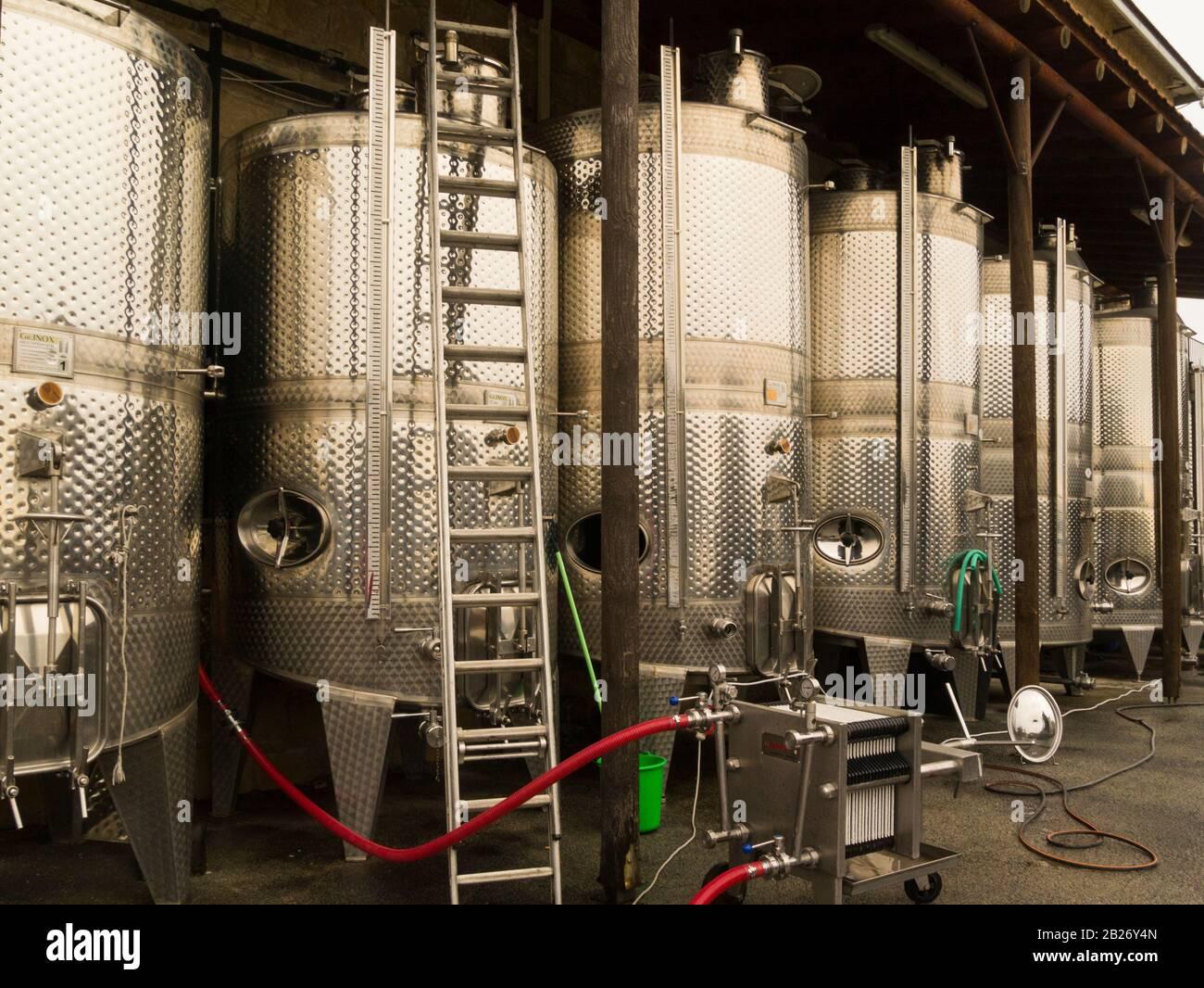 Vats de acero inoxidable que contienen vino fermentante en la bodega Ktima Gerolemo Omodos Cyprus productor de rosa blanca roja y blanco dulce y RE Foto de stock