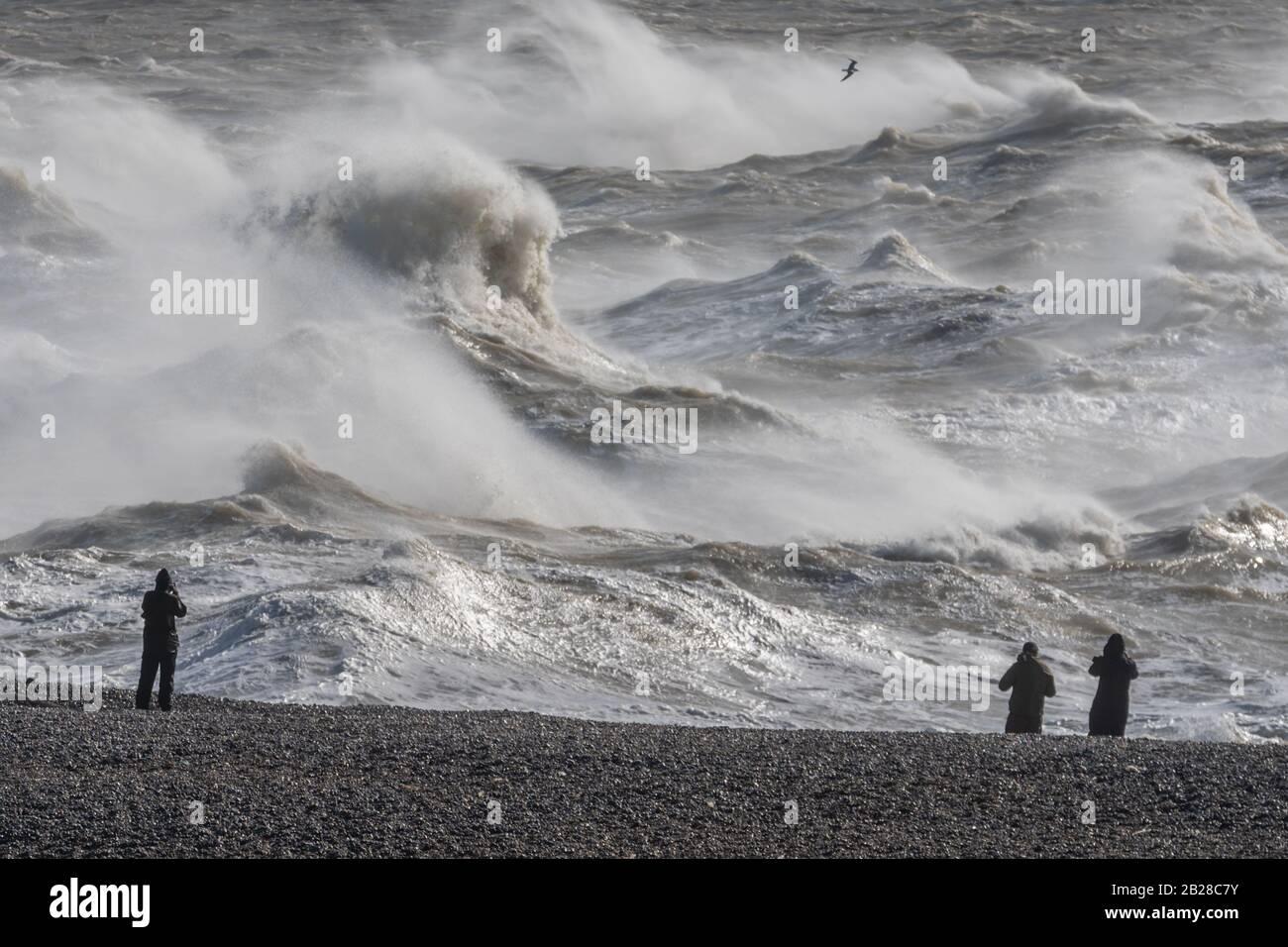 Fotógrafos bordean la playa de Newhaven, East Sussex, mientras la tormenta Jorge desata vientos fuertes y fuertes lluvias el 29 de febrero de 2020. Foto de stock
