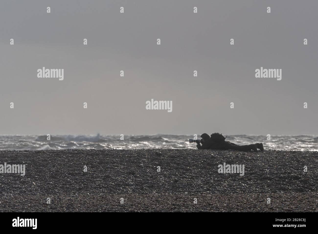 Un fotógrafo que toma fotografías de las condiciones extremas en la costa sur de Inglaterra cuando la tormenta Jorge se acerca el 29 de febrero de 2020. Foto de stock