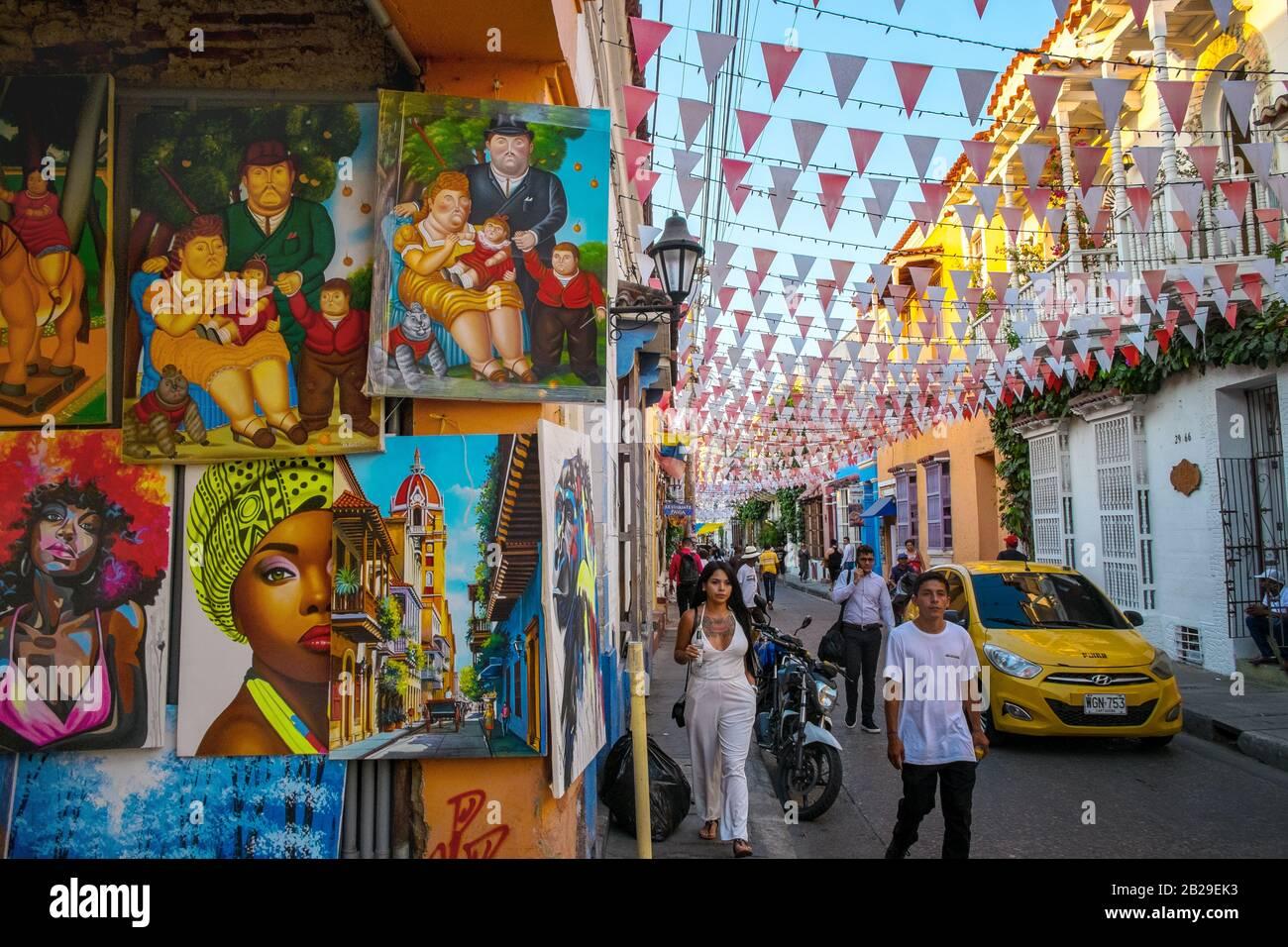 Los peatones caminan por las pinturas para la venta en un estudio artístico en el Barrio Getsemaní, Cartagena, Colombia Foto de stock
