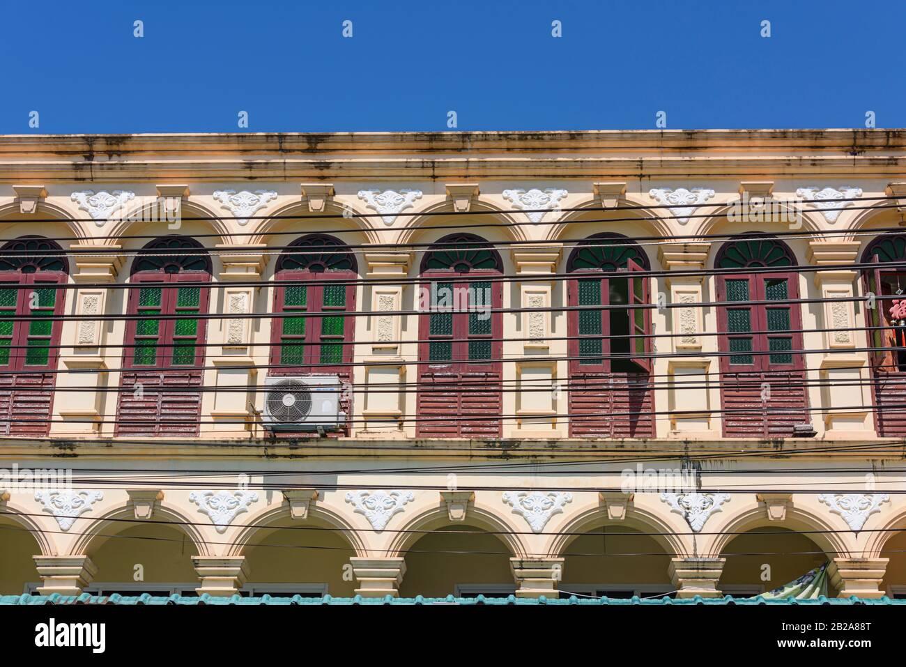 Cables eléctricos estirados frente a un edificio sino-portugués con muchas ventanas, Tailandia Foto de stock