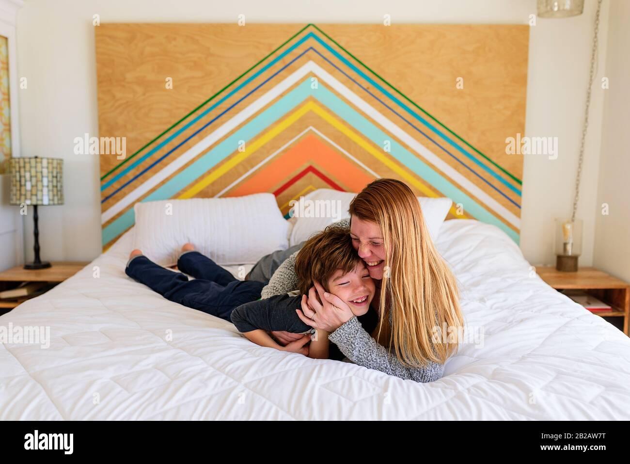 Feliz madre e hijo acostado en una cama que se cuddling Foto de stock