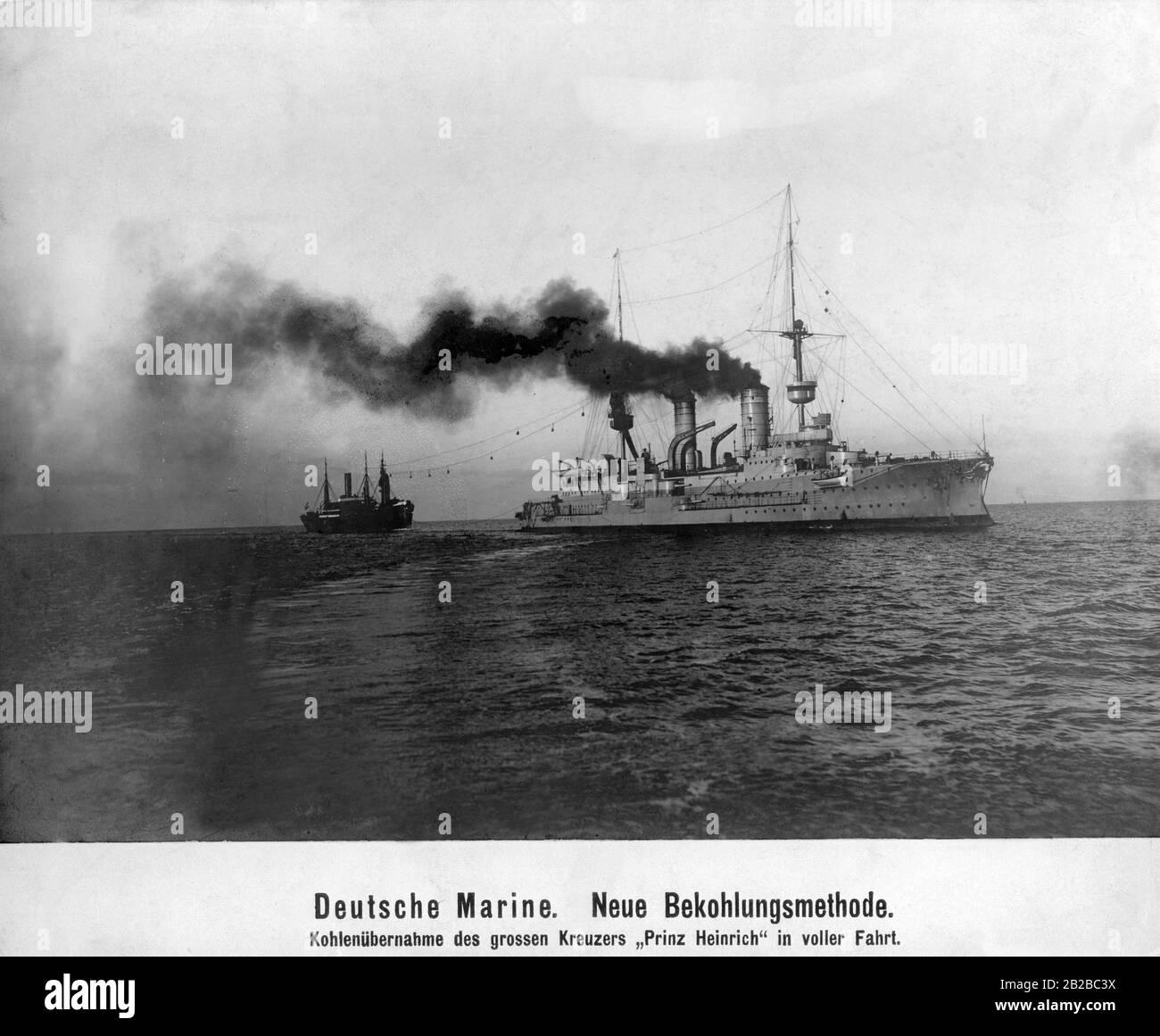 """El pesado crucero alemán """"Prinz Heinrich"""" en alta mar está practicando con un barco de pesca un nuevo método de tomar el carbón en alta mar. Aquí se intenta transferir las bolsas de carbón del barco de transporte al crucero mediante una conexión de cable. Foto de stock"""