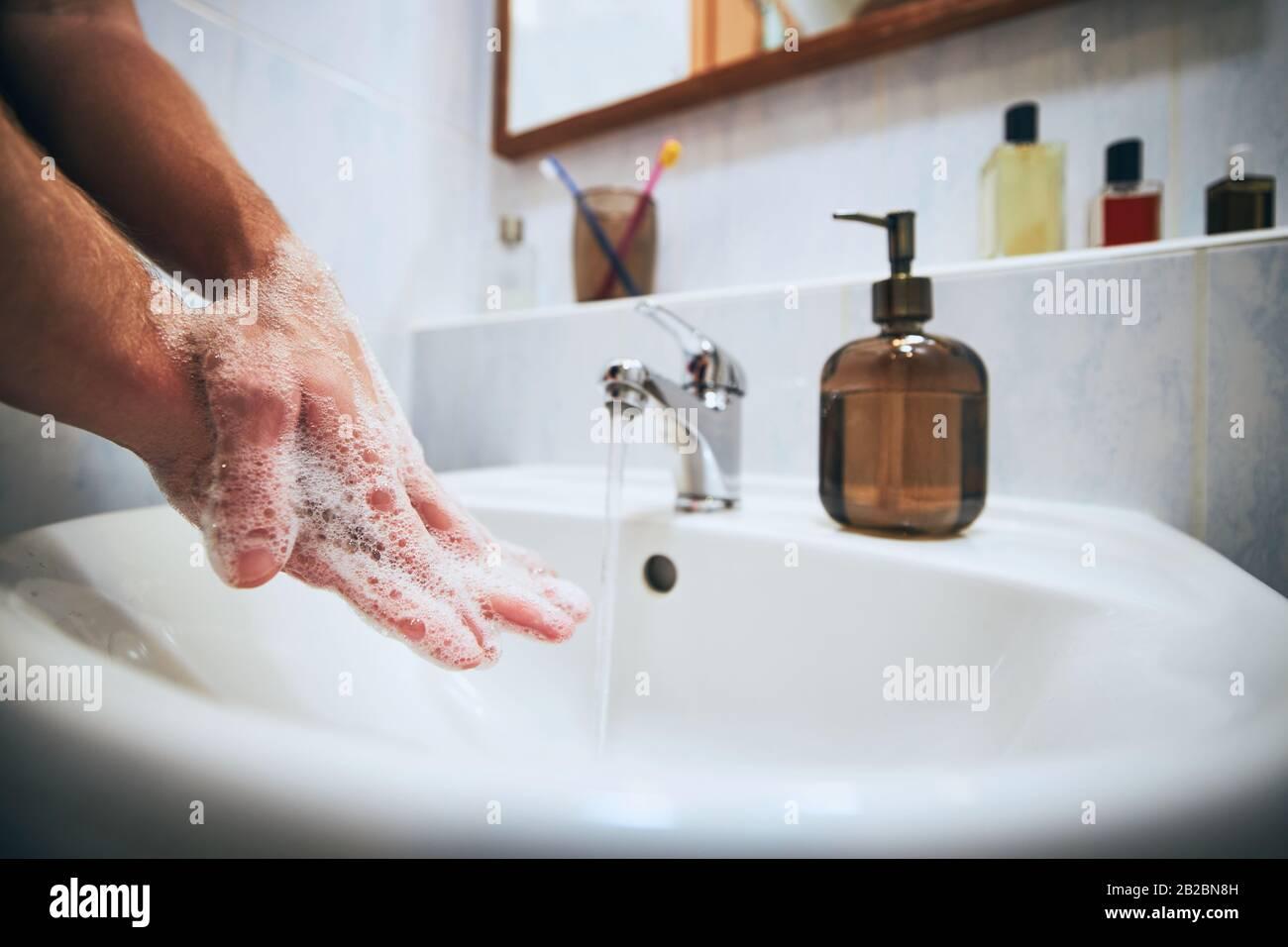 Lavarse las manos en casa en el cuarto de baño. Estilo de vida saludable, higiene y prevención de enfermedades virales y bacterianas. Foto de stock