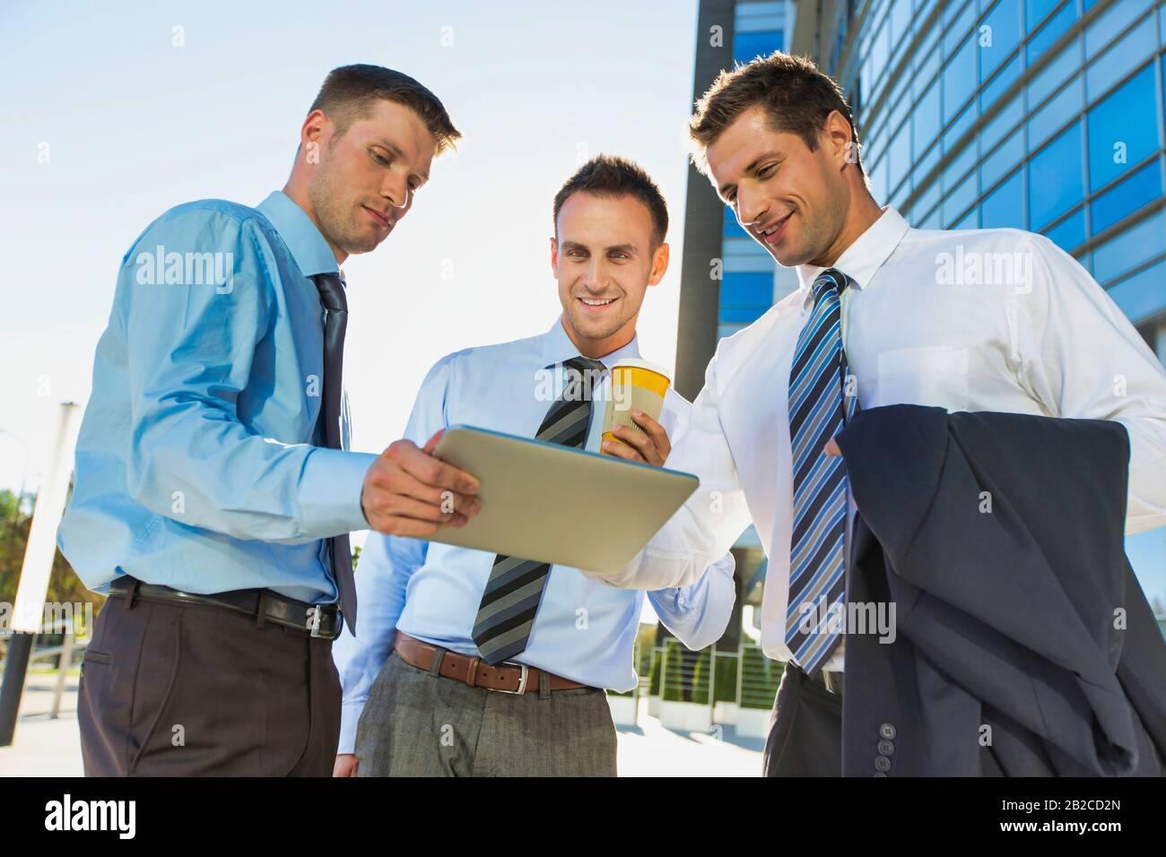 Empresario maduro y atractivo que muestra y discute planes sobre tabletas digitales con colegas contra el edificio de oficinas Foto de stock