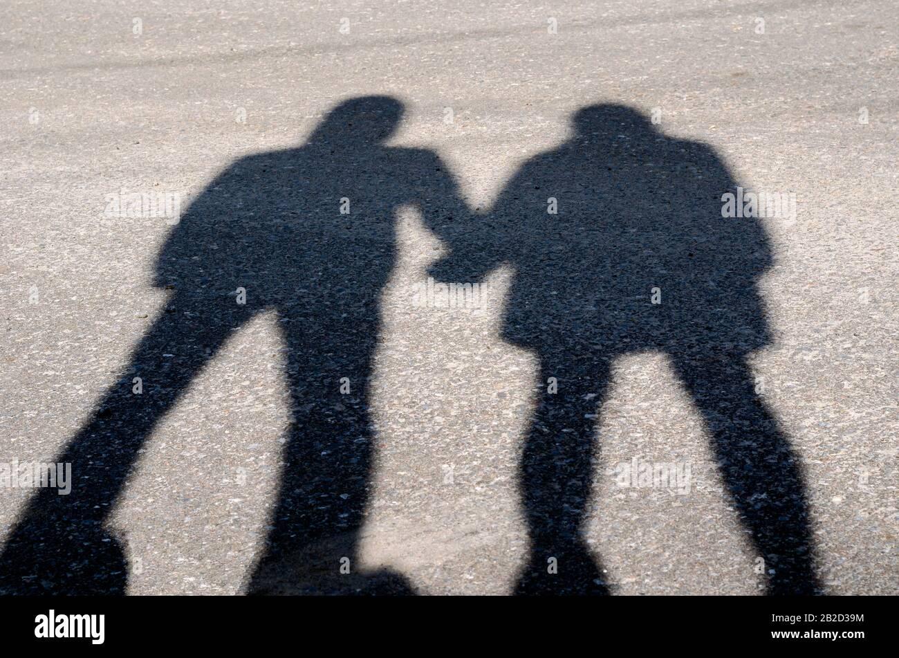Serie de siluetas de jóvenes amantes. Serie 1. La sombra de los amantes de la mano al atardecer. Un chico y una niña están de pie cerca sosteniendo las manos. Sh Foto de stock