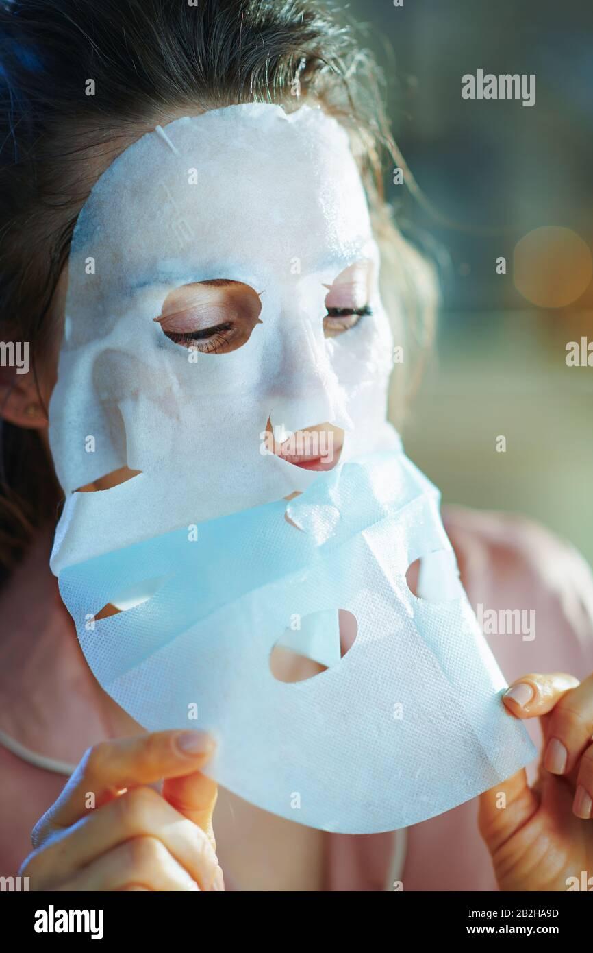 mujer joven en pijamas en el salón moderno en el soleado día de invierno aplicando una máscara facial de hoja y quitando la capa protectora. Foto de stock