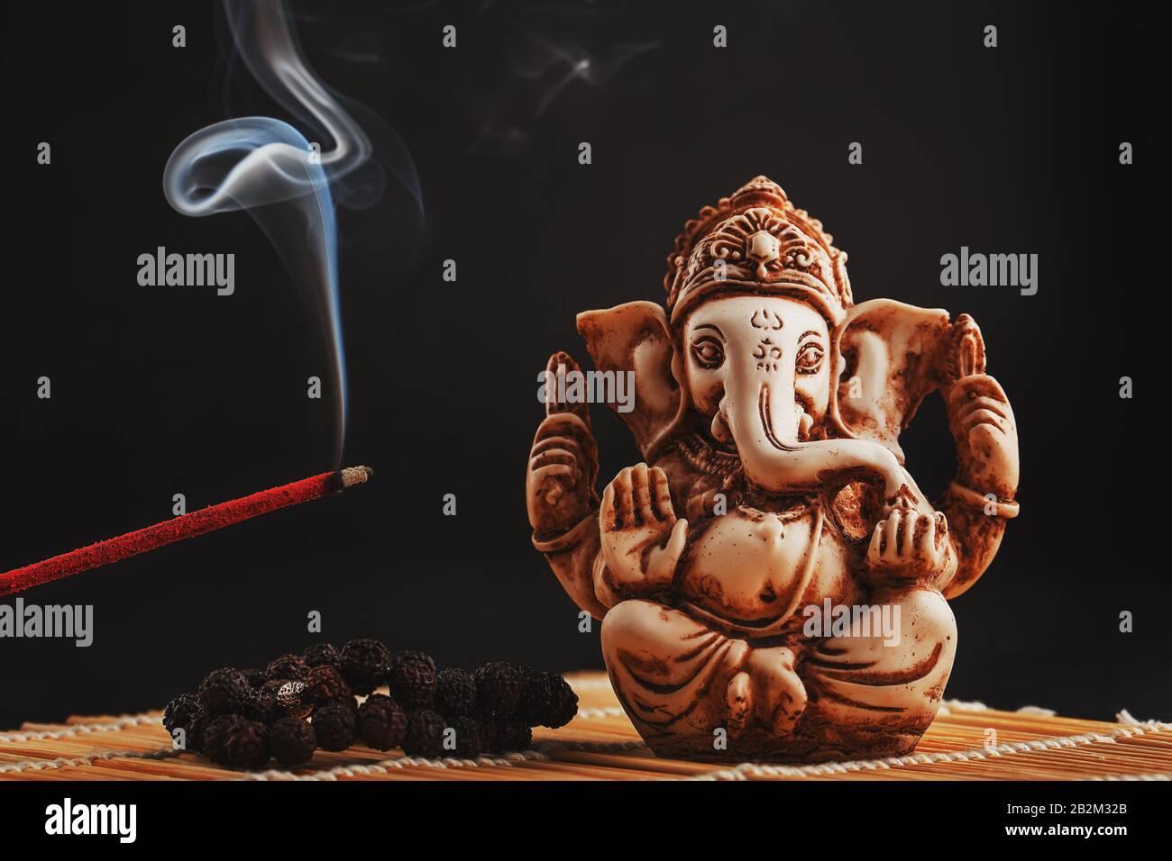 dios hindú Ganesh sobre un fondo negro. Estatua de Rudraksha y rosario en una mesa de madera con un palo de incienso rojo y humo de incienso. Espacio de copia Foto de stock