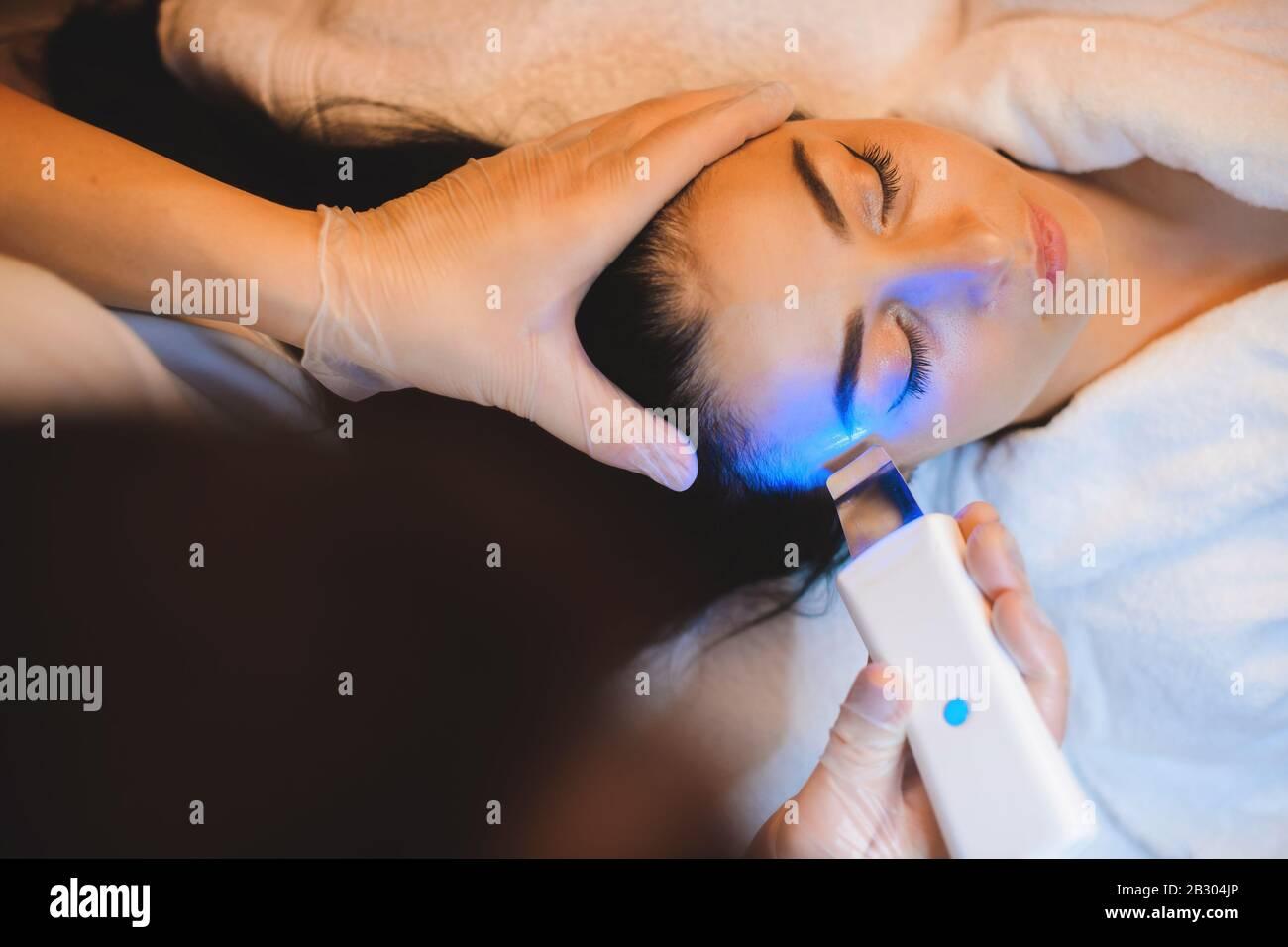 Un dermatólogo cuidadoso está teniendo una sesión de láser con una señora caucásica morena Foto de stock