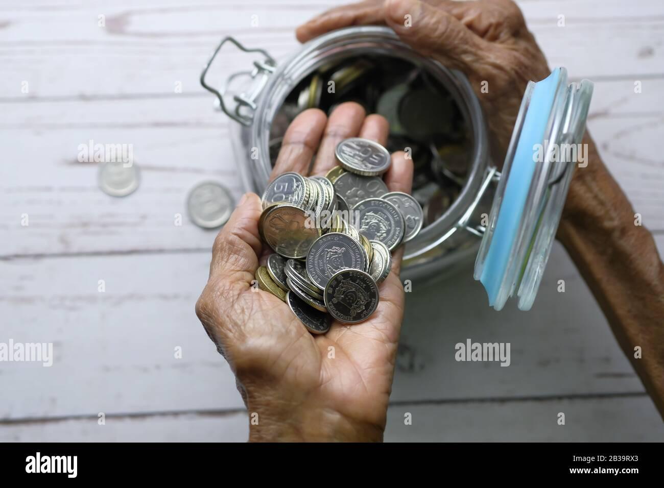 vista superior de las mujeres mayores ahorro monedas en un frasco Foto de stock