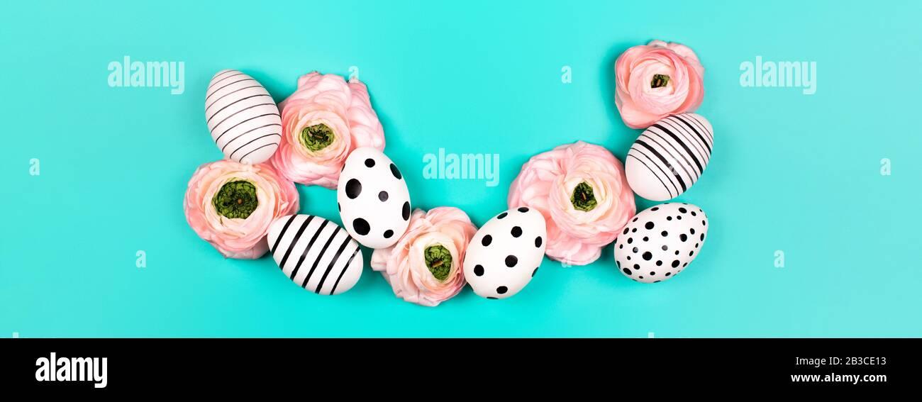Gráfico creativo huevos pintados a mano y ranunculus flores sobre fondo azul pastel. Concepto de Pascua. Lugar para el texto. Foto de stock