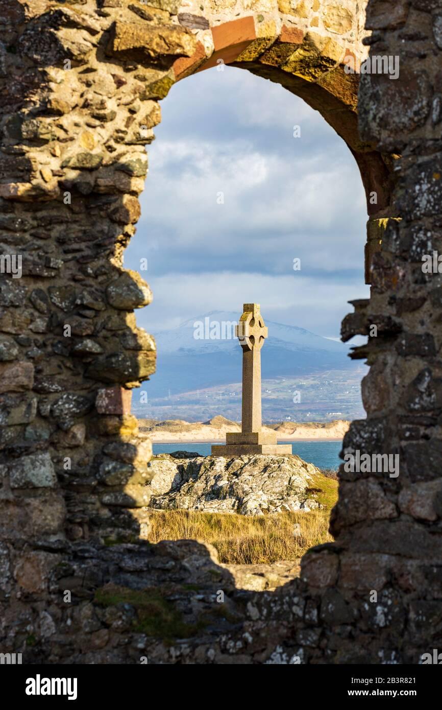 La cruz celta se ve a través de las ruinas de la iglesia de San Dwynwen en la isla de Llanddwyn, Anglesey Foto de stock