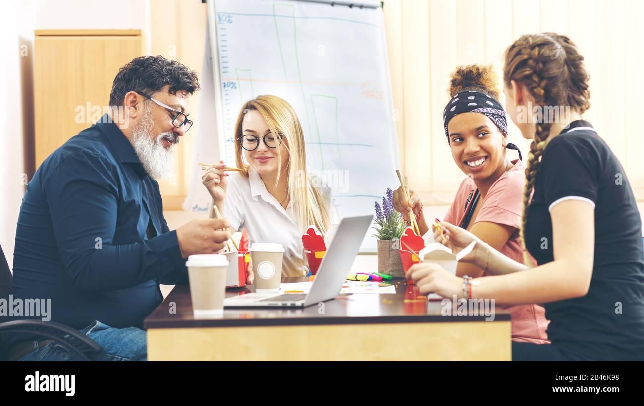 Multi-étnico grupo empleados disfrutar de comida para llevar la conversación amistosa en Office Foto de stock