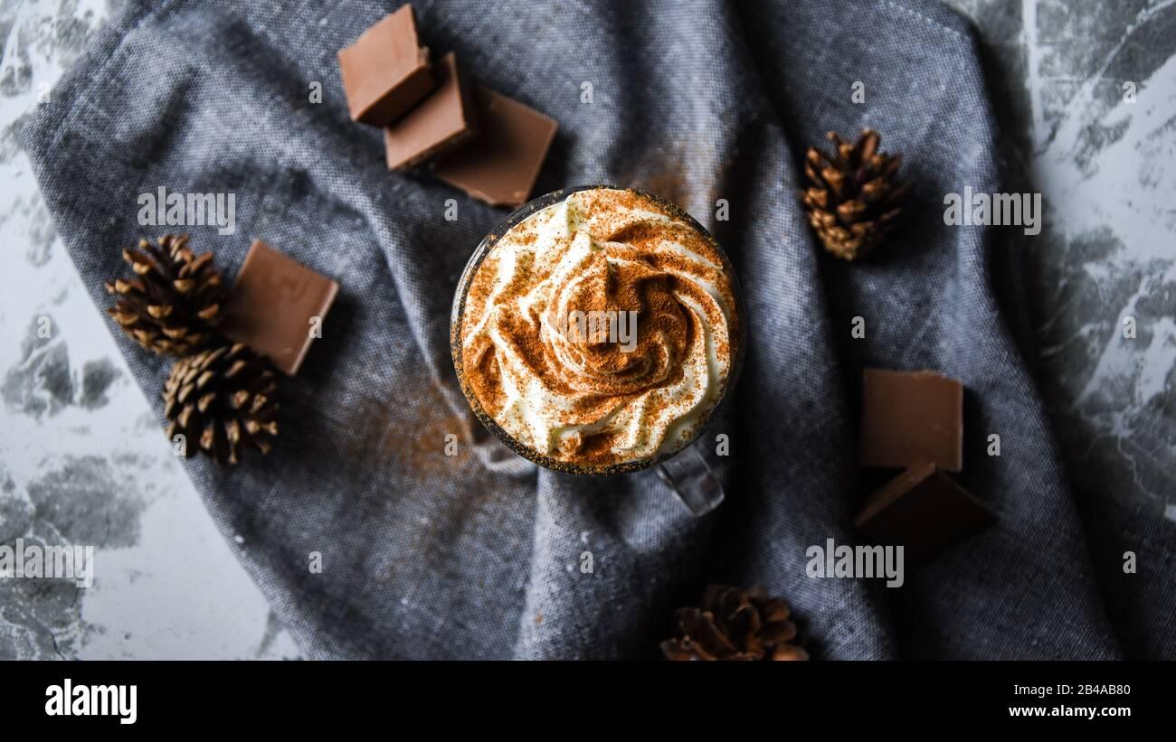 Café helado con crema sobre mesa rústica, bebida de café en una taza transparente con chocolate Foto de stock