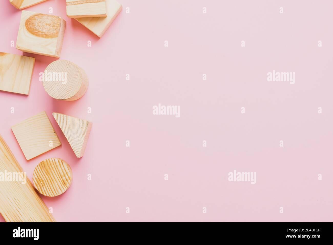 Juguetes de madera para niños sobre un concepto de fondo rosa cero al oeste. Marco de cubos en desarrollo. Espacio de copia. Diseño plano de vista superior. Foto de stock