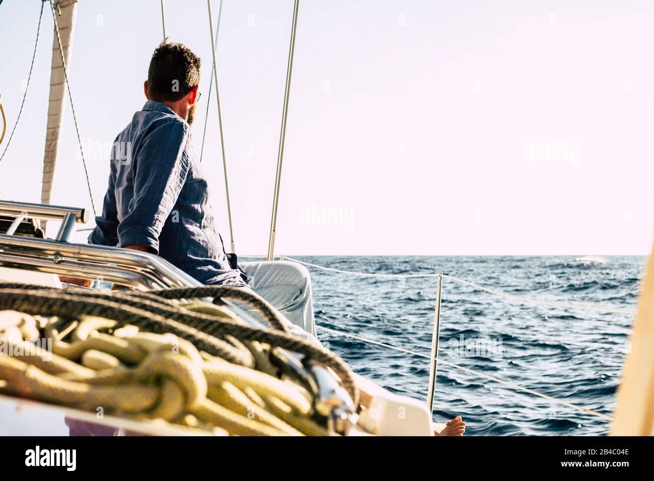 Hombre libre disfrutando de la actividad de ocio al aire libre en un barco de vela con el océano azul alrededor - concepto de vacaciones de verano de lujo - gente feliz navegando con la naturaleza y buen tiempo Foto de stock