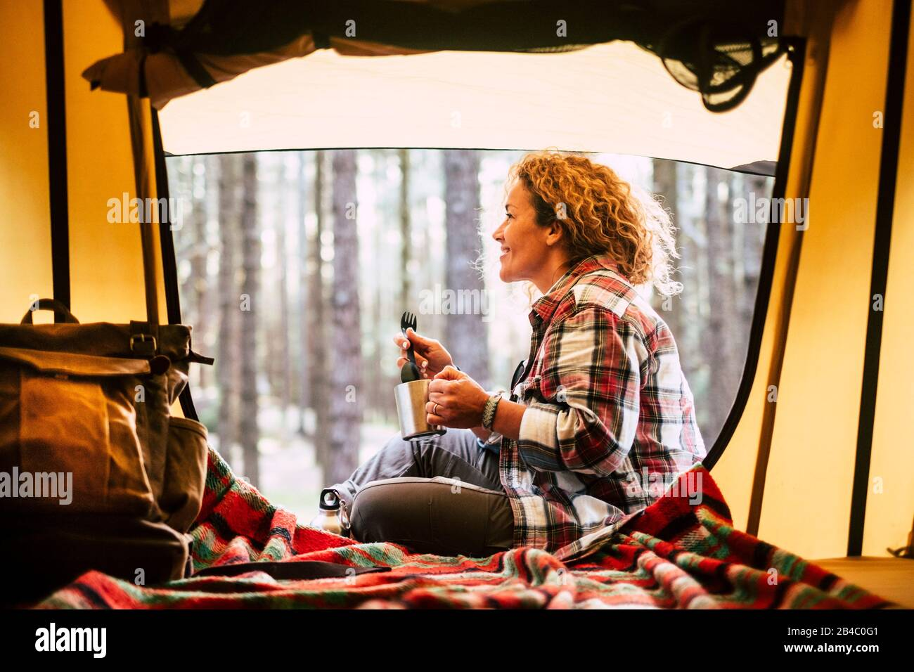 Camping con tienda de campaña y aventura viajes alternativos concepto de vacaciones con gente alegre - hermosa sonrisa rubia adulto y disfrutar de la naturaleza al aire libre alrededor del bosque sentarse cerca de una mochila y beber café Foto de stock