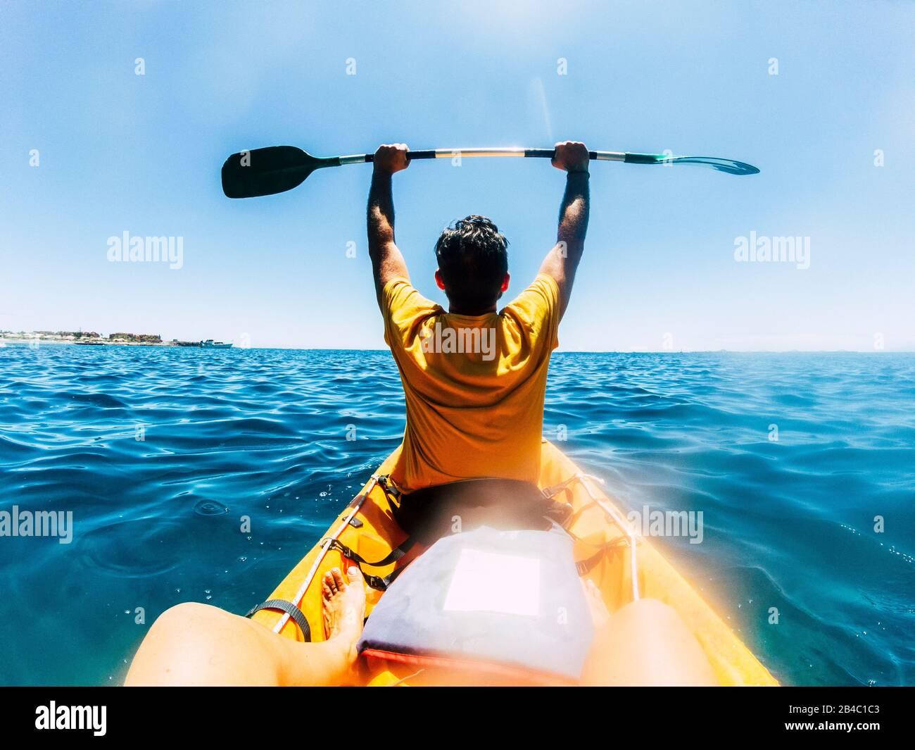Viajar y disfrutar del estilo de vida de la gente en vacaciones de verano disfrutando de una excursión con kayak en el océano azul - felicidad y libertad pareja en el mar al aire libre actividad de ocio juntos Foto de stock