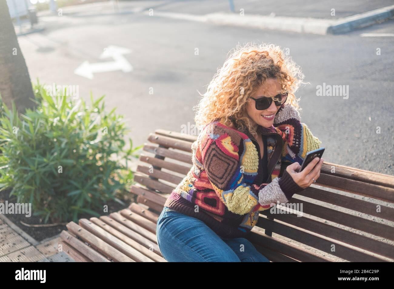 mujer sola en la calle sentada en un banco del parque usando su teléfono y sonriendo en él - concepto de estilo de vida en línea - rizado rubio hermosa chica con la tecnología de dispositivo a. permanezca conectado con la gente Foto de stock